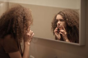serious young lady touching face while looking at mirror in 3974065 1 300x200 Lupus Awareness Month